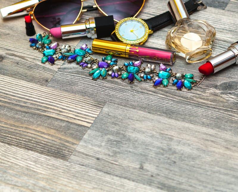 Gestileerde vrouwelijke flatlay met glazen, lippenstift, parfum, horloge, tegenhanger, gestreept overhemd en spot omhoog op witte royalty-vrije stock foto's