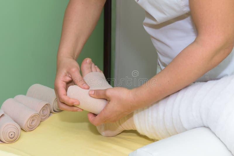 Gestione dei linfonodi: Agitare la gamba utilizzando bende multistrato per controllare il linfonedema Parte della terapia deconge fotografia stock