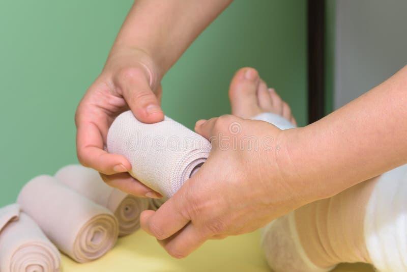 Gestione dei linfonodi: Agitare la gamba utilizzando bende multistrato per controllare il linfonedema Parte della terapia deconge immagine stock libera da diritti