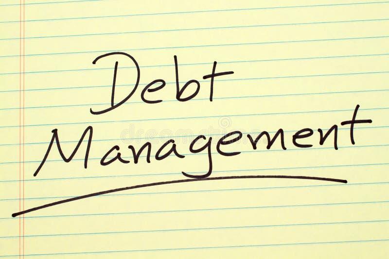 Gestione di debito su un blocco note giallo immagine stock