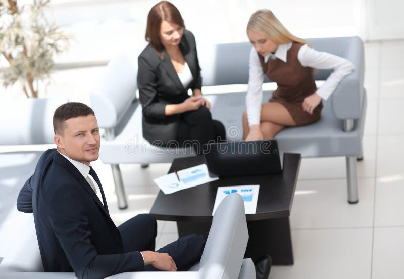 Gestionnaire financier s'asseyant à côté des collègues et regardant l'appareil-photo image libre de droits