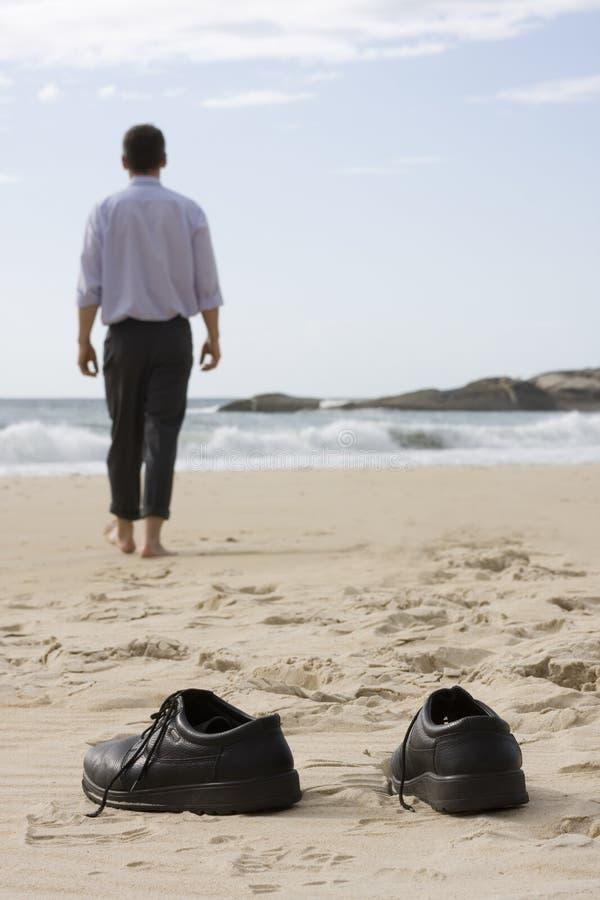 Gestionnaire marchant nu-pieds sur la plage image libre de droits