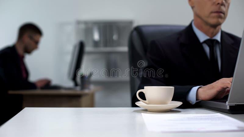 Gestionnaire travaillant sur ordinateur portable, tasse de café debout sur table, concept amateur de travail photographie stock