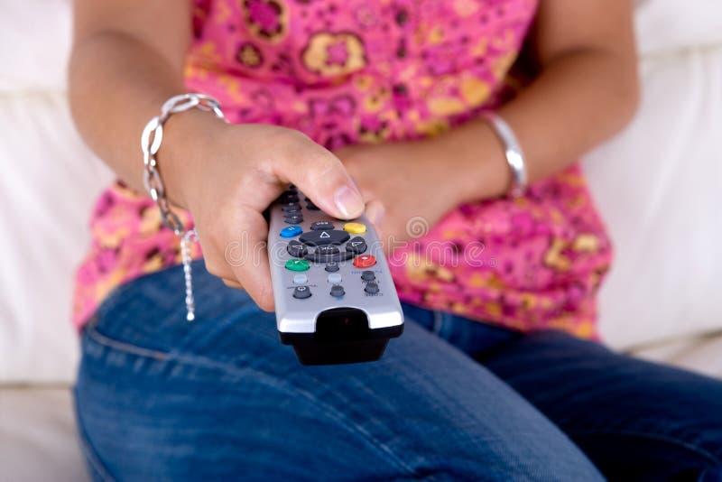 gestisca i giovani a distanza della donna della televisione della holding fotografie stock libere da diritti