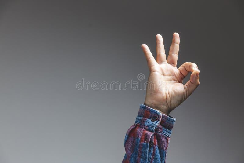 gesto adulto masculino da aprovação da exibição da mão no tiro do estúdio isolado no fundo cinzento fotografia de stock