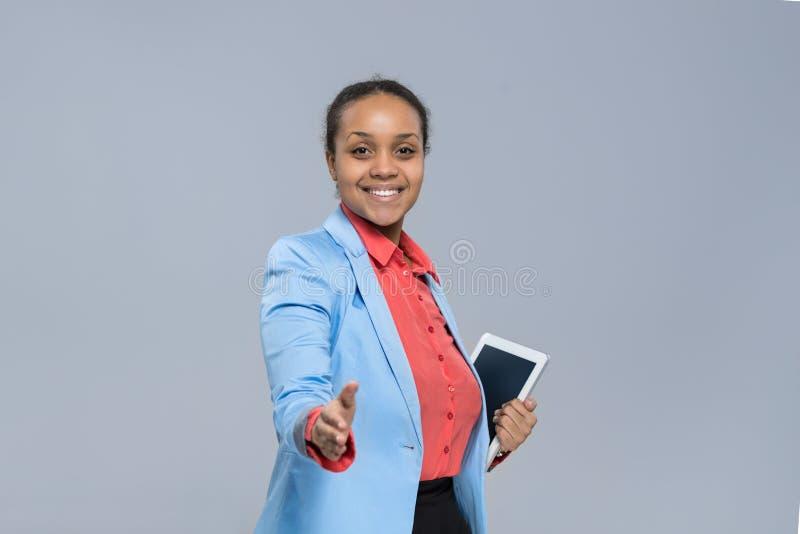 Gesto afro-americano da boa vinda do aperto de mão da menina do tablet pc novo da posse da mulher de negócio imagem de stock royalty free
