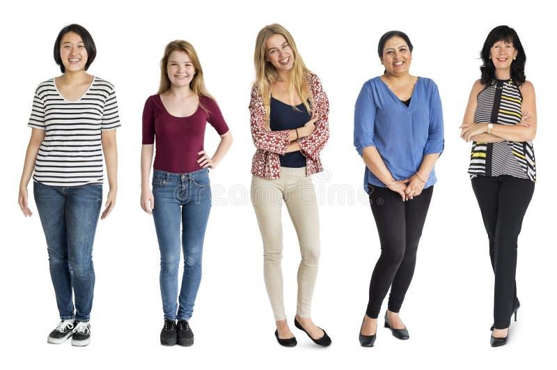 Gesto ajustado mulheres da diversidade que está junto o estúdio isolado foto de stock