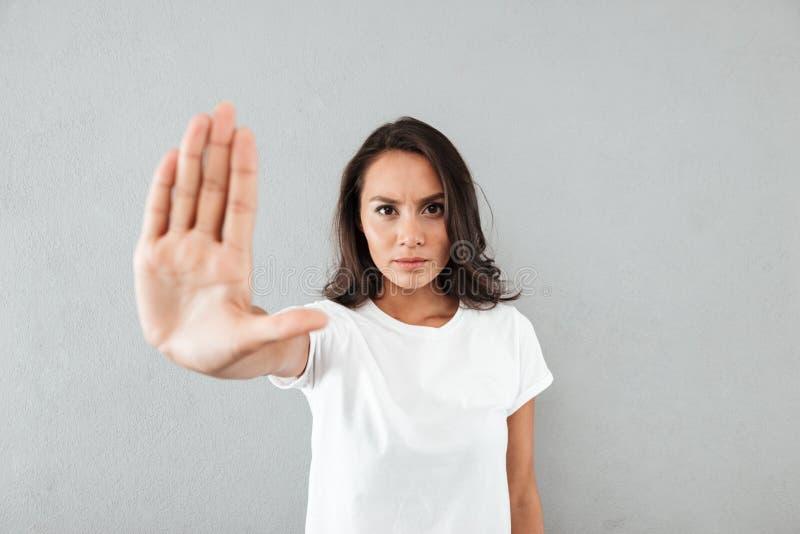 Gesto asiático novo sério da parada da exibição da mulher com sua palma fotografia de stock