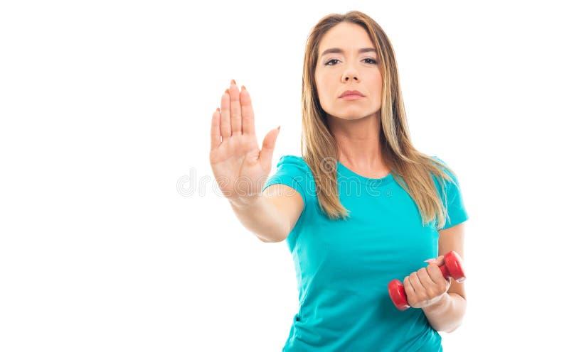 Gesto d'uso di arresto di rappresentazione della maglietta della giovane ragazza graziosa fotografie stock libere da diritti