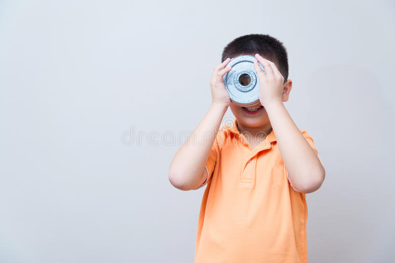 Gesto de gracejo do menino asiático que veste os vidros falsificados feitos com dum do ferro fotografia de stock