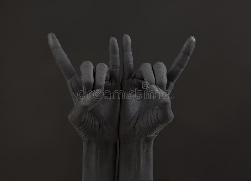 Gesto de la cabra en un fondo oscuro Mano negra que hace símbolo de la roca Manos para arriba en un concierto de rock fotos de archivo