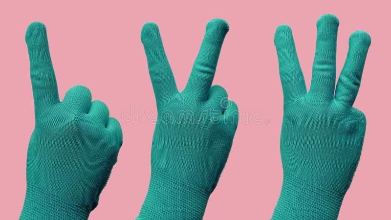 Gesto de mão como um dois três em luvas verdes fotos de stock