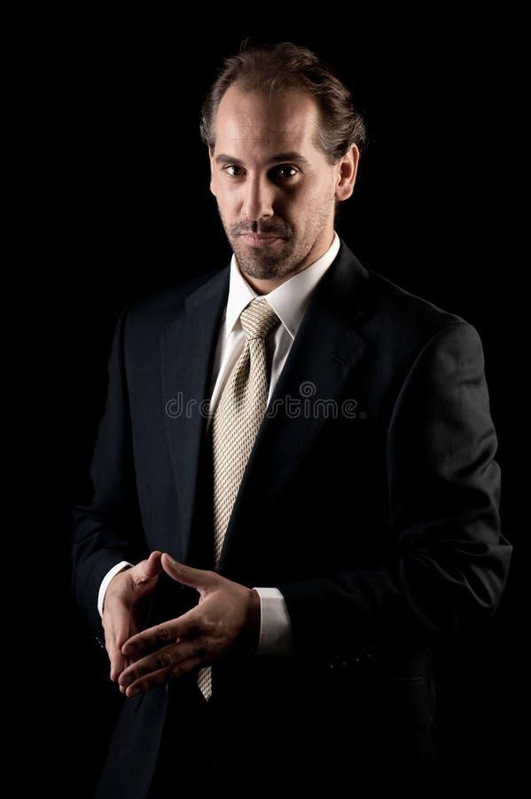 Gesto de mãos sério do homem de negócios adulto no preto fotos de stock royalty free