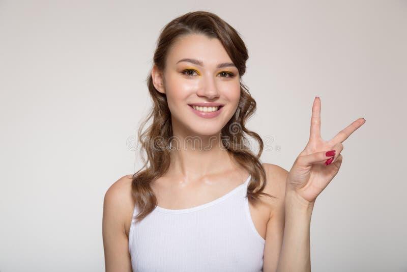 Gesto de sorriso novo da exibição da mulher sobre o fundo claro Dois dedos acima fotografia de stock royalty free