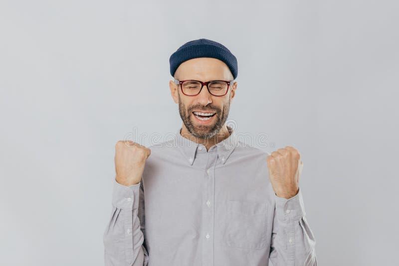 Gesto del éxito El hombre sin afeitar extático jubiloso aumenta los puños apretados, lleva gafas y la camisa formal, celebra el s imagenes de archivo