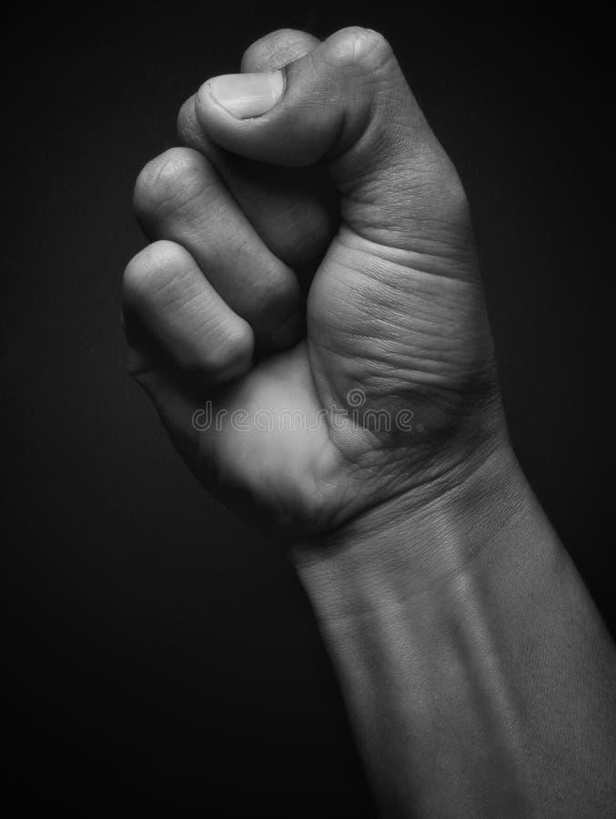 Gesto del pugno della mano isolato su fondo nero Tenuta maschio della mano fotografie stock
