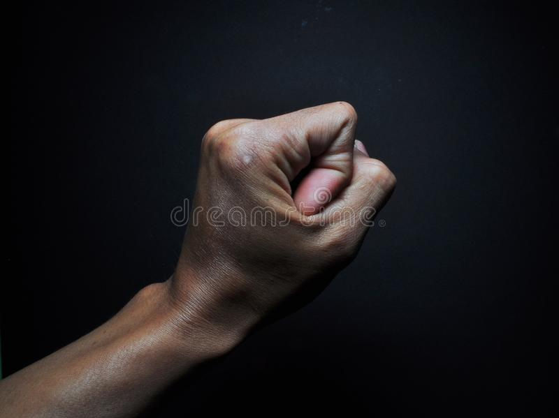 Gesto del pugno della mano isolato su fondo nero Tenuta maschio della mano immagine stock