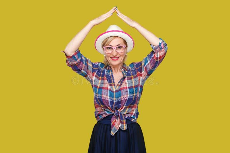 Gesto del tetto sulla testa Ritratto della donna matura alla moda moderna felice nello stile casuale con la condizione del cappel immagini stock libere da diritti