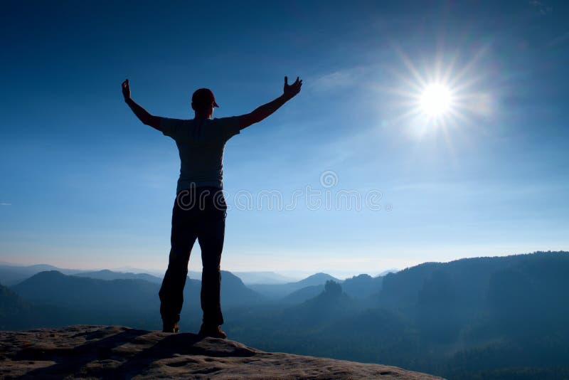 Gesto del trionfo Viandante felice in abiti sportivi L'uomo alto sul picco della roccia dell'arenaria in orologio della Sassonia  fotografia stock libera da diritti