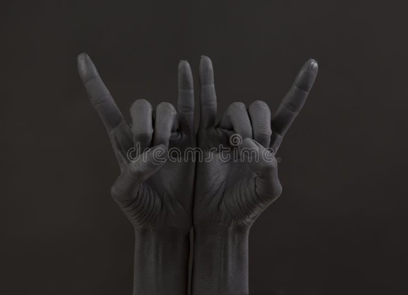 Gesto della capra su un fondo scuro Mano nera che fa simbolo della roccia Mani su ad un concerto rock fotografie stock