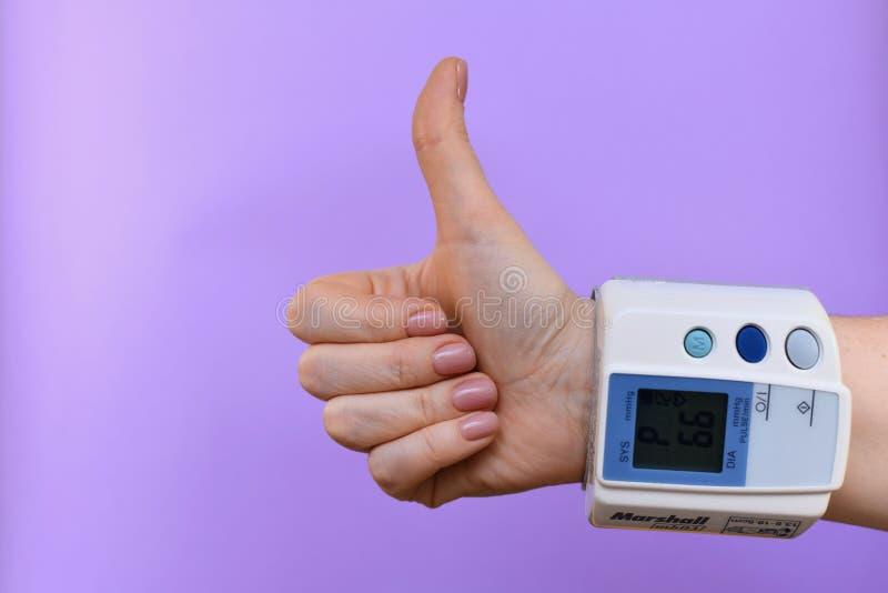 Gesto di mano con un tonometer sul polso fotografia stock libera da diritti