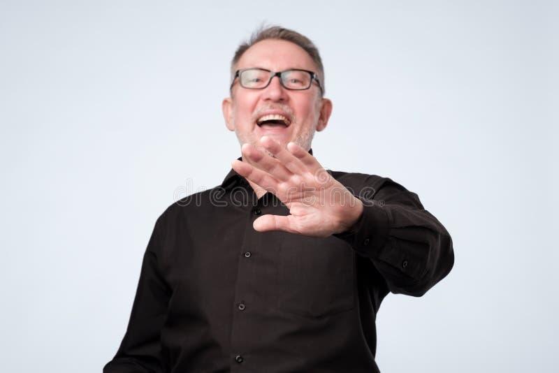 Gesto di risata di arresto di rappresentazione dell'uomo senior, chiedente di smettere di scherzare immagine stock libera da diritti