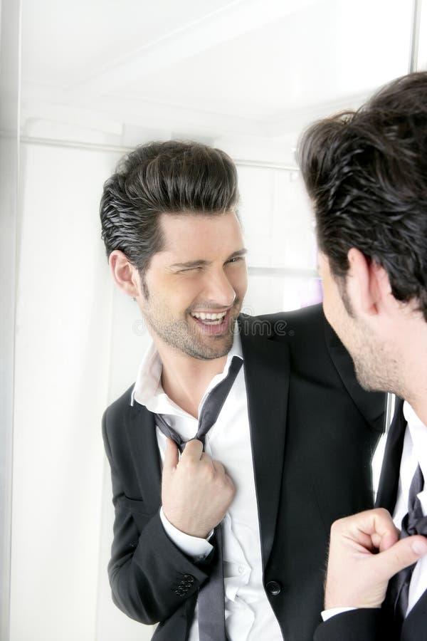 Gesto divertido del humor hermoso del hombre en un espejo fotos de archivo