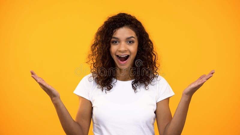 Gesto fêmea afro-americano novo na câmera, boa notícia da exibição uau, surpresa fotos de stock