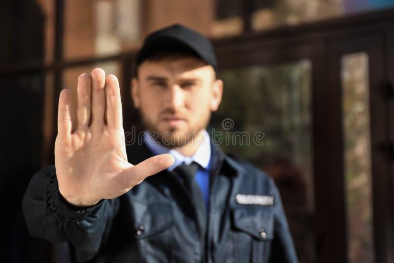 Gesto masculino de la parada de la demostración del guardia de seguridad al aire libre foto de archivo libre de regalías