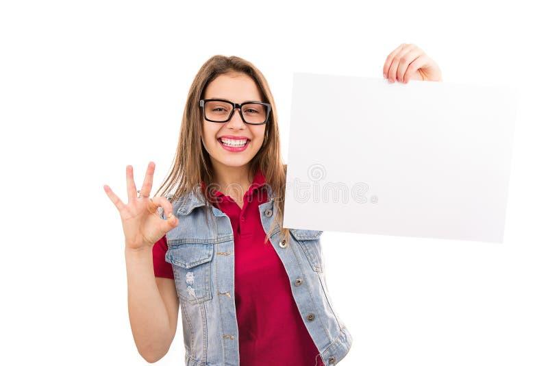 Gesto sorridente di APPROVAZIONE di rappresentazione della donna con carta in bianco fotografie stock libere da diritti