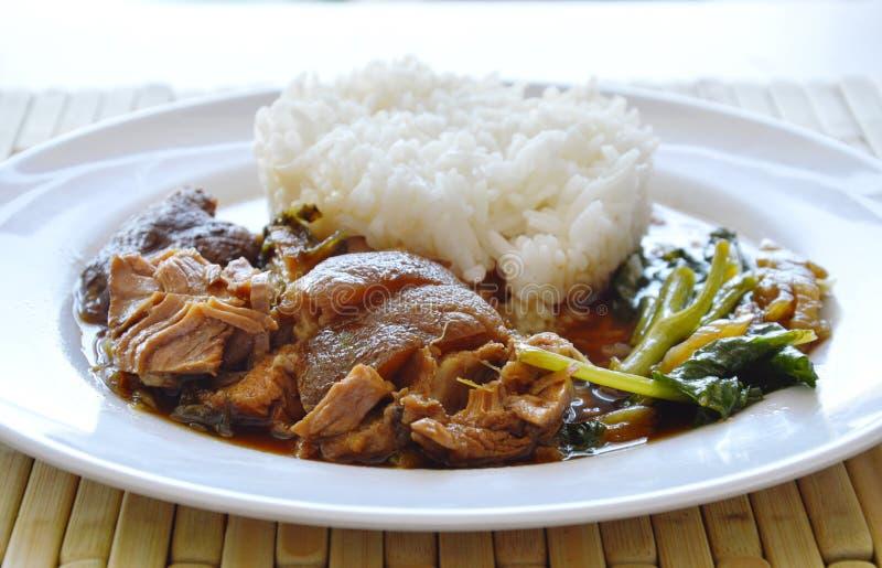 Gestoofd varkensvleesbeen met rijst op schotel stock foto's