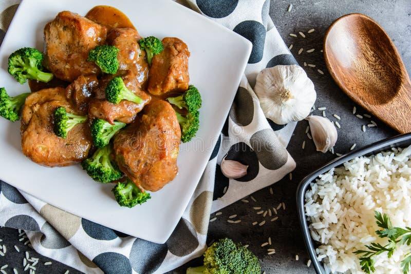 Gestoomd varkensvlees met balsemieke azijn en geroosterde broccoli en rijst stock afbeeldingen