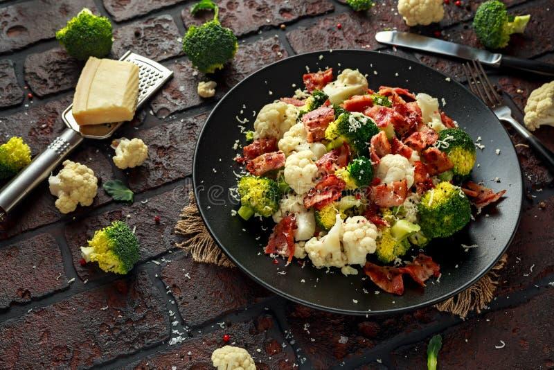 Gestoomde Broccoli, Bloemkoolsalade met Bacon, parmezaanse kaaskaas in een zwarte plaat Gezond voedselconcept royalty-vrije stock foto's