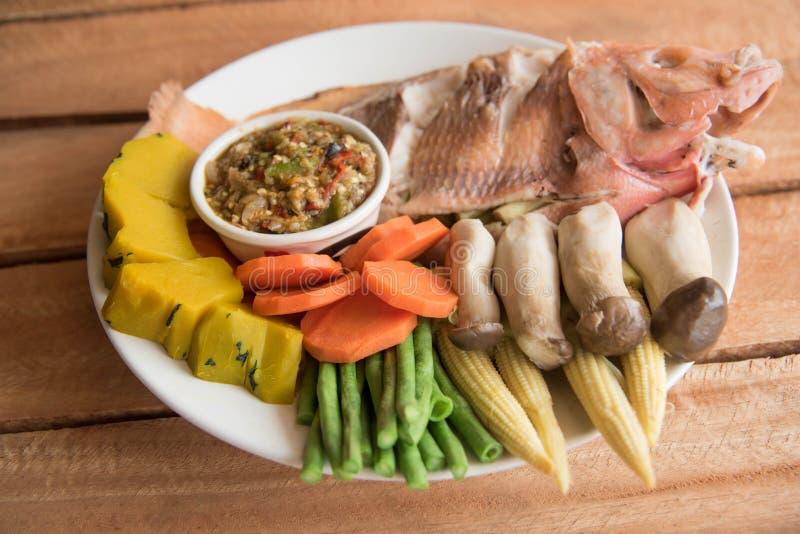 Gestoomde die tilapia van Nijl vissen en groenten, met saus worden gediend stock afbeeldingen