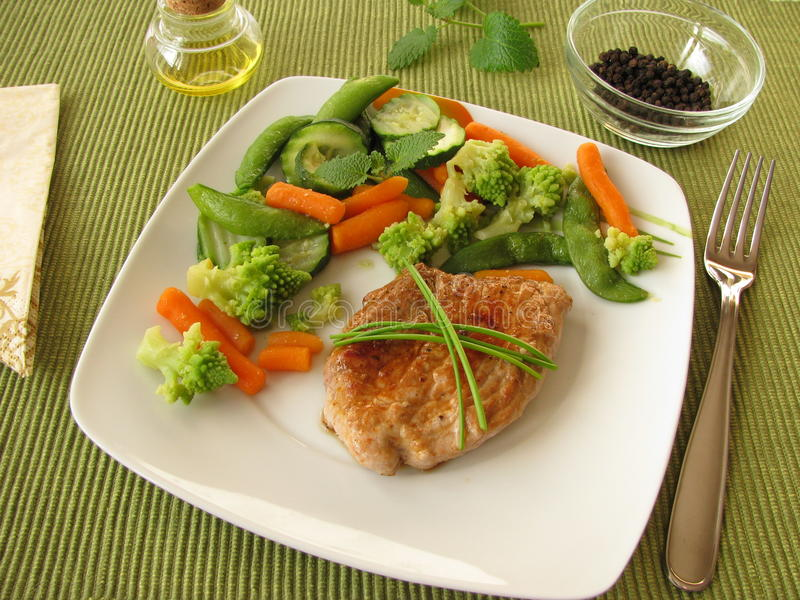 Gestoomde groente met varkensvleeskotelet stock afbeeldingen