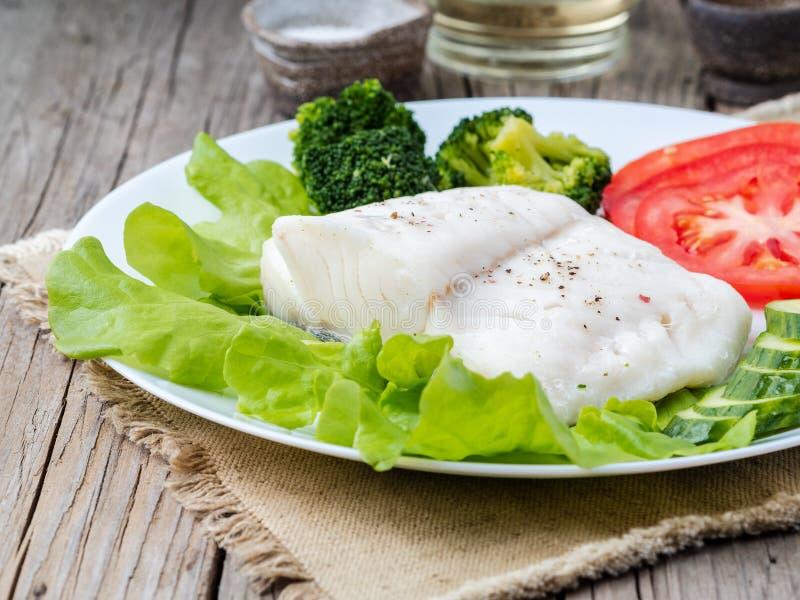 Gestoomde kabeljauwvissen Paleo, keto, fodmap gezonde voeding met groenten op witte plaat op houten lijst, zijaanzicht royalty-vrije stock fotografie