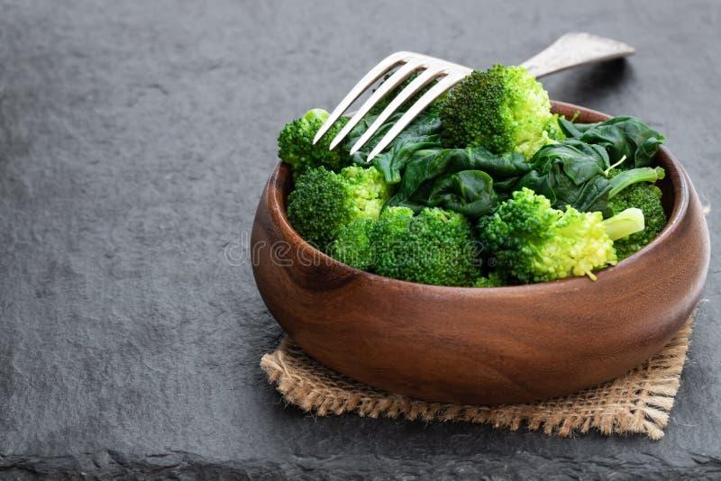 Gestoomde verse broccoli met spinazie op zwarte steenachtergrond stock afbeelding