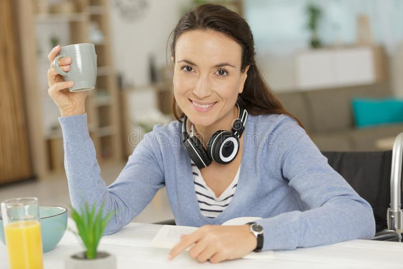 Gestor de escritório feliz na cadeira de rodas que come o chá ou o café imagem de stock royalty free