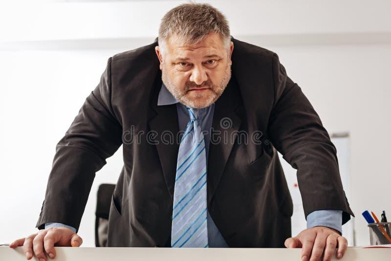Gestor de escritório oprimido assustador que é furioso foto de stock