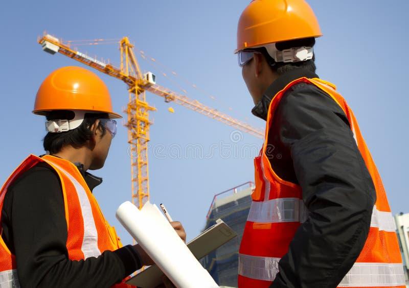 Trabalhadores da construção com o guindaste no fundo imagens de stock