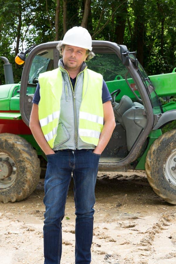 gestor de local considerável na frente de uma máquina escavadora imagens de stock royalty free