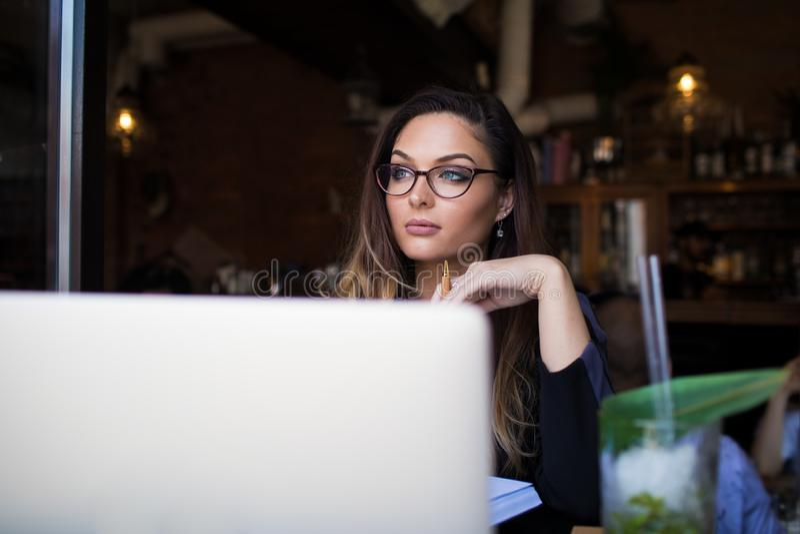 Gestor de proyecto de sexo femenino que sueña durante trabajo vía netbook fotos de archivo