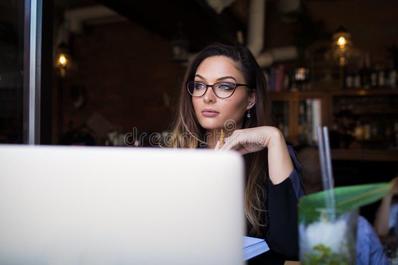 Gestor de proyecto de sexo femenino que sueña durante trabajo vía netbook imagen de archivo