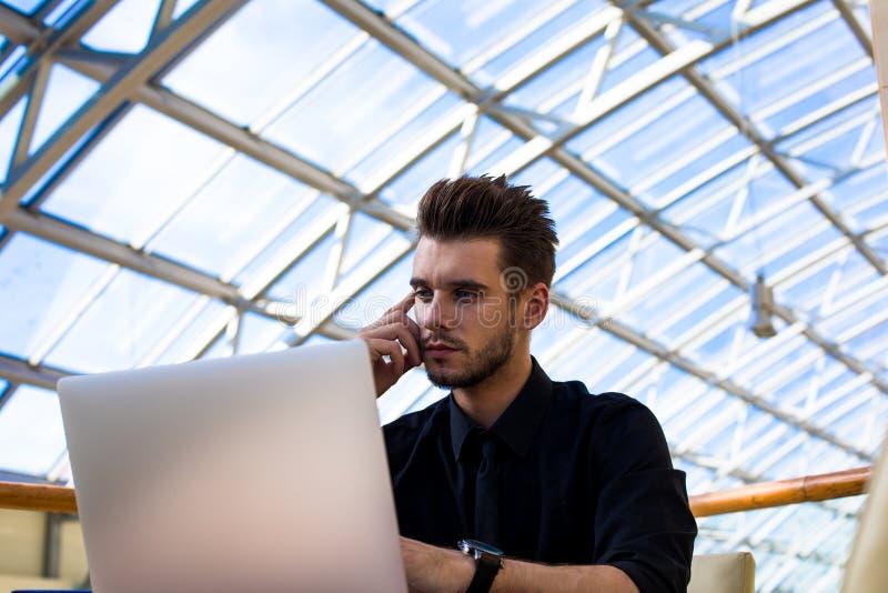 Gestor de proyecto de sexo masculino serio que tiene webinar en el dispositivo del cuaderno de la PC fotografía de archivo libre de regalías