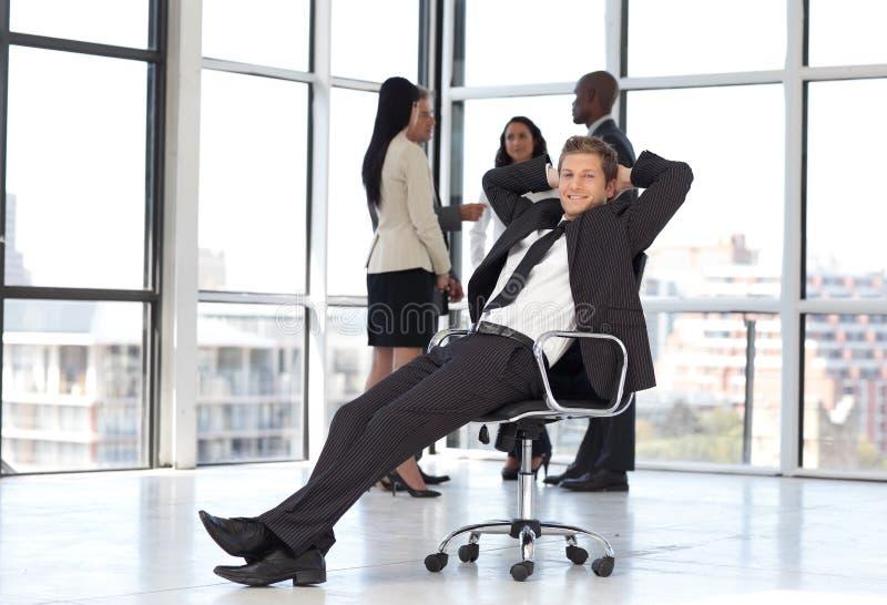 Gestore che si distende nell'ufficio con la squadra nella priorità bassa fotografia stock libera da diritti