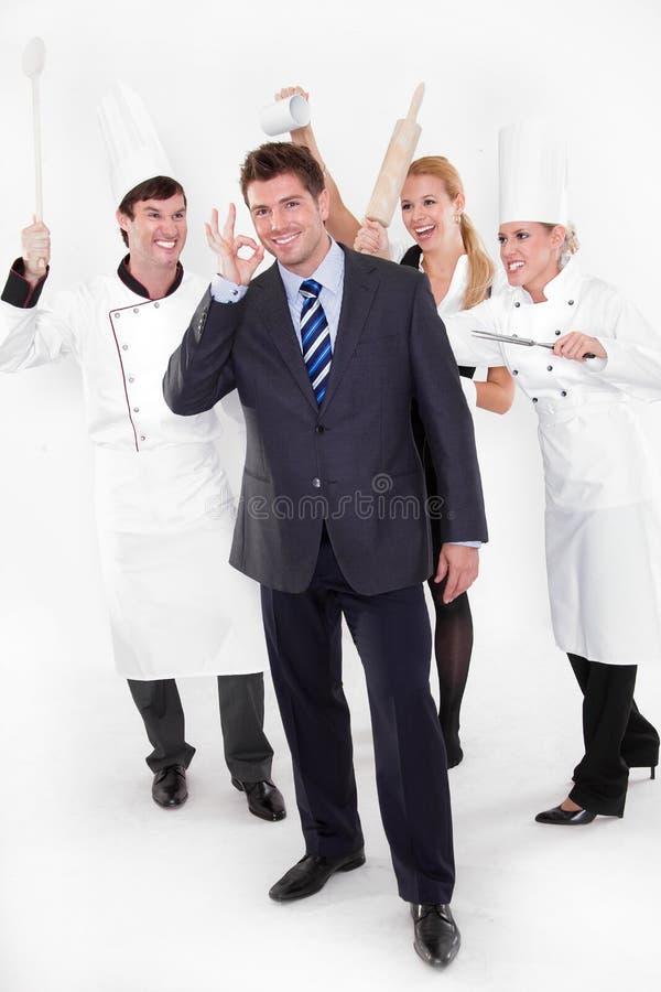 Gestore del ristorante con il personale pazzesco dietro fotografia stock libera da diritti