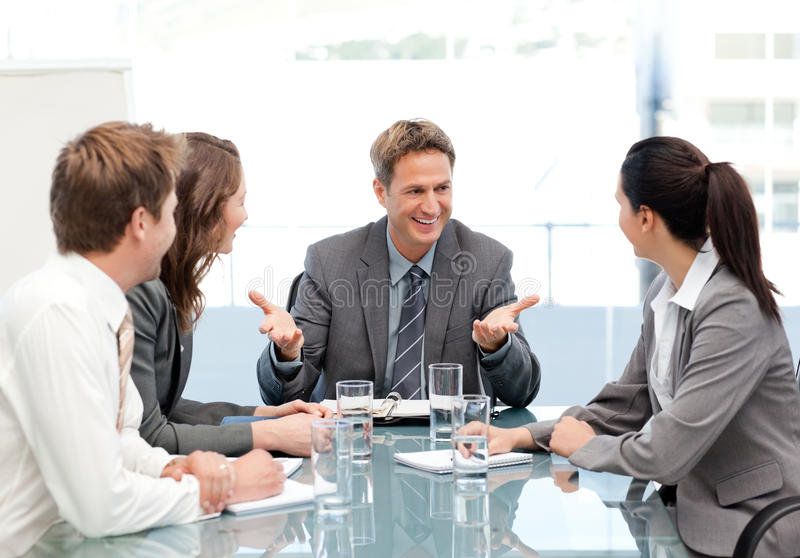 Gestore di Cheeful che comunica con sua squadra ad una riunione fotografie stock
