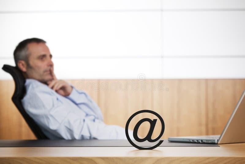 Gestore di Ofifce che contempla circa il commercio elettronico. fotografia stock