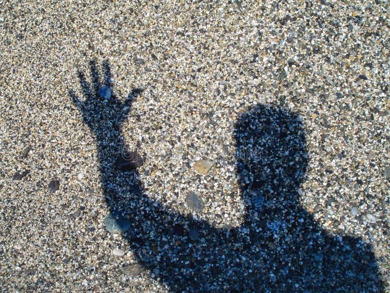 Gestos da silhueta da mão no fundo da areia do mar imagens de stock royalty free