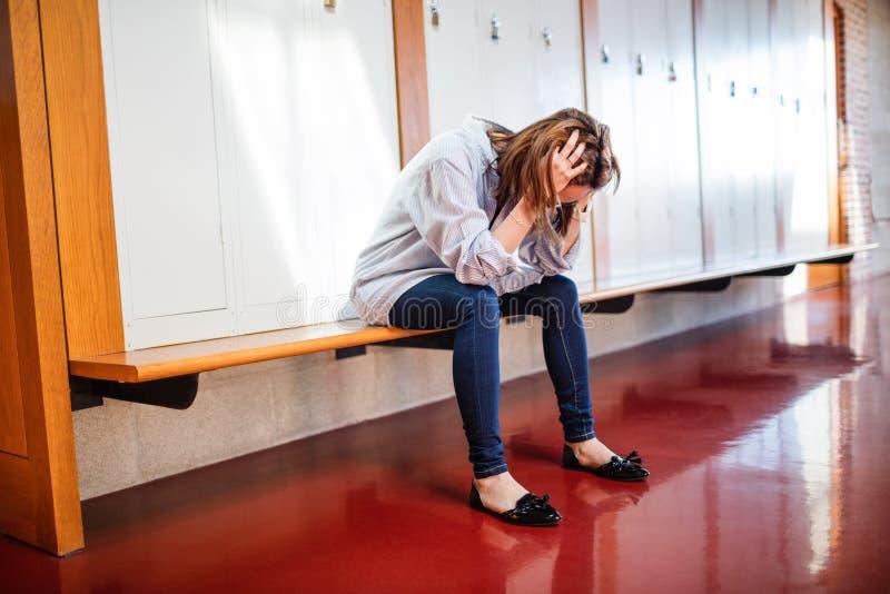 Gestraffte Frau, die im Umkleideraum sitzt stockfoto